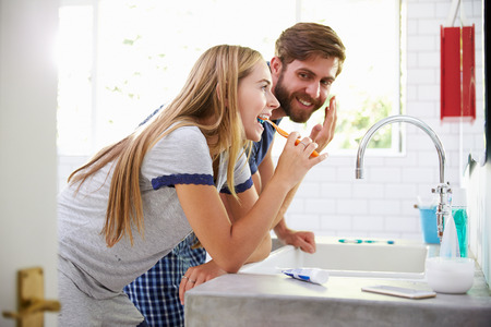 dientes: Pareja en pijamas Cepillar los dientes y ponerse crema hidratante Foto de archivo