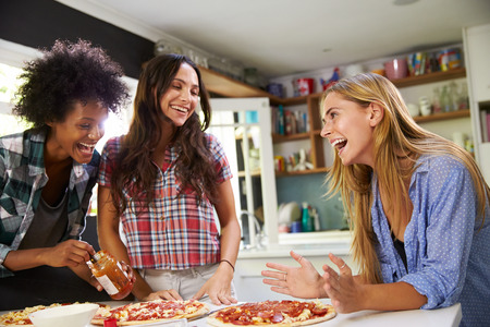 Three Female Friends Making Pizza In Kitchen Together Stock Photo