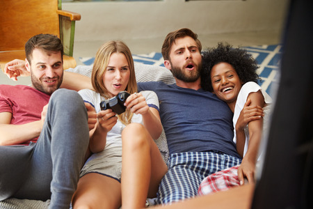 video game: Group Of Friends Wearing Pajamas Playing Video Game Together