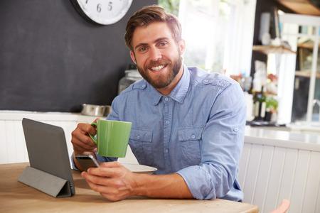 El hombre que come el desayuno durante el uso de la tableta digital y teléfono