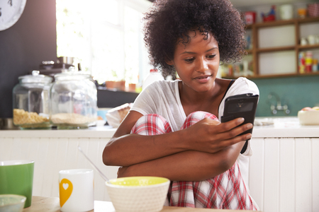 african coffee: Young Woman Eating Breakfast Whilst Using Mobile Phone