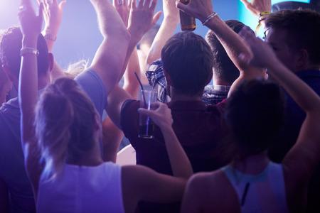 jovenes tomando alcohol: Vista posterior de personas bailando en club nocturno