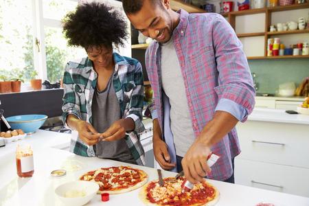 mujeres cocinando: Pareja joven que hacen la pizza en cocina Juntos Foto de archivo