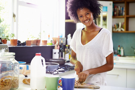 comiendo cereal: Mujer joven en pijama preparan el desayuno en la cocina
