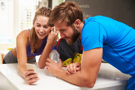 Couple Wearing Gym Clothing Reading Message On Mobile Phone