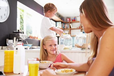 niños desayunando: Madre y niños que desayunan en el vector de cocina