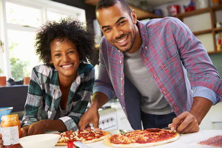 american food: Young Couple Making Pizza In Kitchen Together