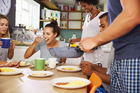 having breakfast: Group Of Friends Enjoying Breakfast In Kitchen Together Stock Photo