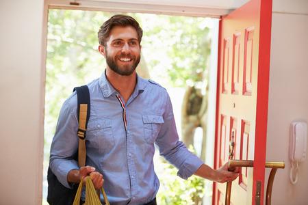 abriendo puerta: Hombre joven que vuelven a casa para el trabajo Con Compras