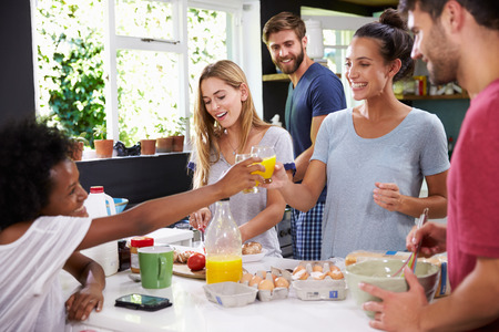 tomato juice: Group Of Friends Cooking Breakfast In Kitchen Together