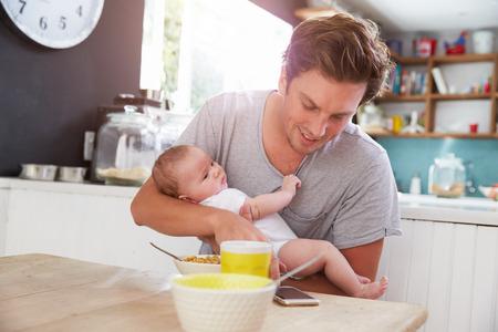 Vater mit Baby-Tochter Überprüfung Handy in der Küche Standard-Bild - 41146823