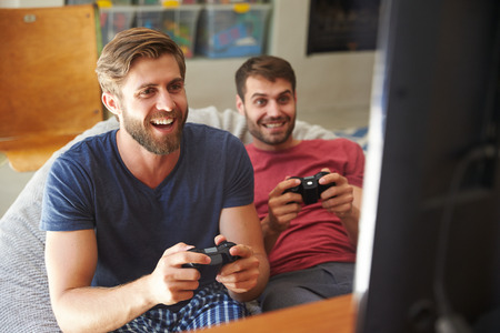 video game: Two Male Friends In Pajamas Playing Video Game Together