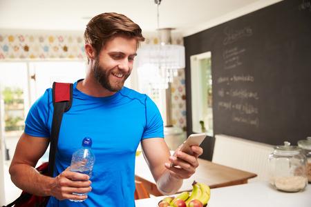 체육관 옷을 입고 남자는 휴대 전화를 찾고 스톡 콘텐츠