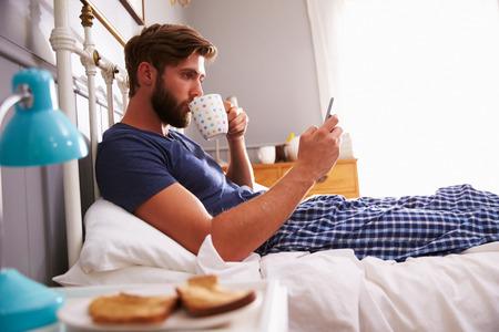 cama: El hombre que come el desayuno en la cama Mientras usa el tel�fono m�vil Foto de archivo