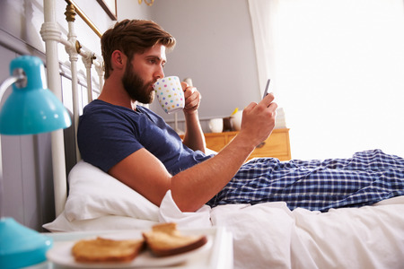 colazione: Man Eating Breakfast In Bed Mentre mezzo del telefono mobile Archivio Fotografico