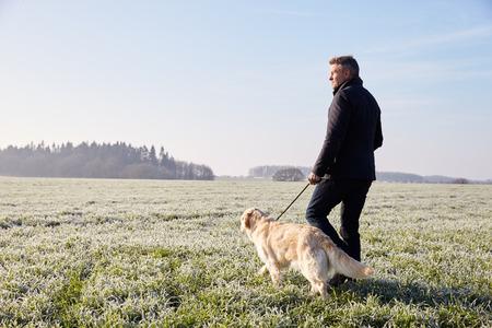 personas caminando: Hombre maduro Perro que recorre en paisaje escarchado