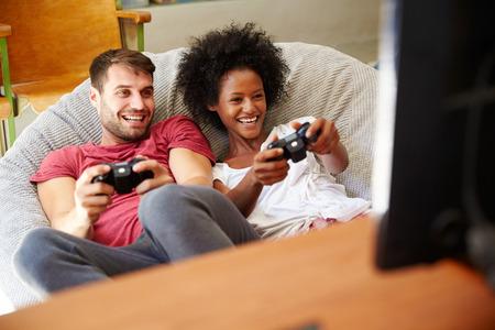 一緒にビデオゲームを遊んでパジャマで若いカップル