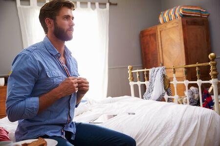 vistiendose: Hombre que se sienta en la cama que Vestirse En la mañana