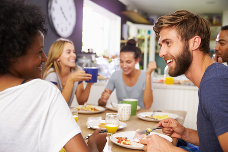 breakfast eggs: Group Of Friends Enjoying Breakfast In Kitchen Together Stock Photo