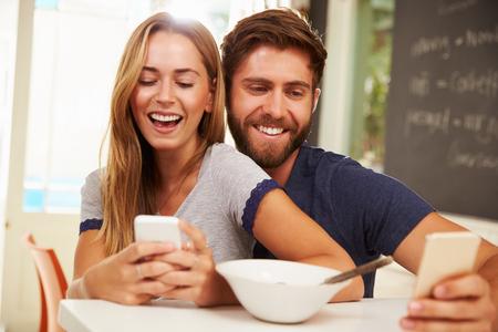 pareja comiendo: Pareja joven que come el desayuno mientras usan los teléfonos móviles