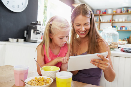 family having fun: Mother And Daughter Using Digital Tablet At Breakfast Table