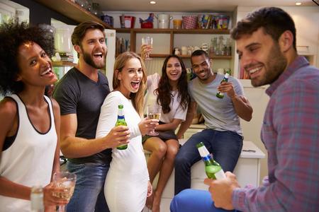 fiesta: Grupo de amigos que disfrutan Bebidas del partido en casa