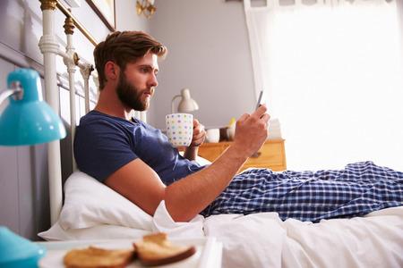 pajamas: El hombre que come el desayuno en la cama Mientras usa el tel�fono m�vil Foto de archivo