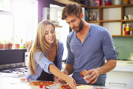 making: Young Couple Making Pizza In Kitchen Together