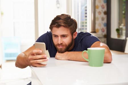 hombre tomando cafe: Hombre joven que bebe caf� y el uso de tel�fono m�vil en el hogar Foto de archivo