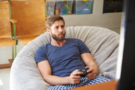 playing video game: Man Wearing Pajamas Sitting In Chair And Playing Video Game