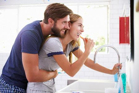 Paar In Pajamas Borstelen tanden in badkamers