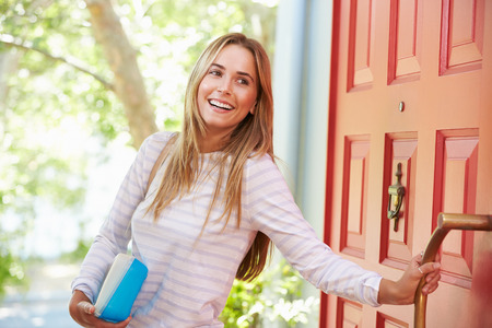 work from home: Young Woman Leaving Home For Work With Packed Lunch Stock Photo
