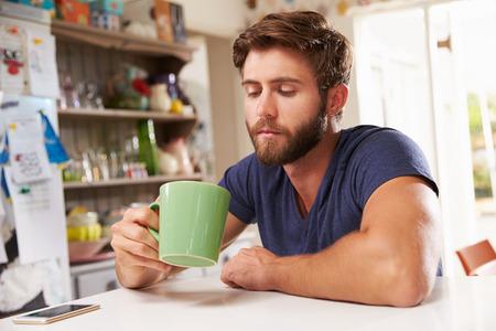 tomando café: Joven Hombre Sentado En La Cocina Mesa de Café Beber Foto de archivo