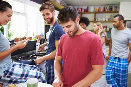 having fun: Group Of Friends Cooking Breakfast In Kitchen Together
