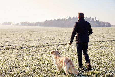 서리가 내린 풍경에서 개를 산책하는 성숙한 남자 스톡 콘텐츠