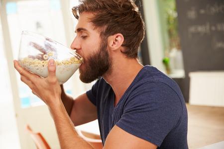 comiendo cereal: Hungry hombre joven que come el desayuno Desde el bol de vidrio Foto de archivo