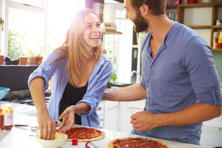 parejas felices: Pareja joven que hacen la pizza en cocina Juntos Foto de archivo