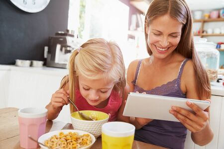 morning breakfast: Mother And Daughter Using Digital Tablet At Breakfast Table