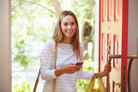 abriendo puerta: Mujer joven que vuelven a casa para el trabajo Con Compras
