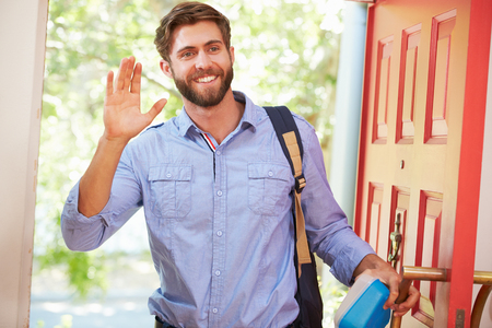 work from home: Young Man Leaving Home For Work With Packed Lunch Stock Photo