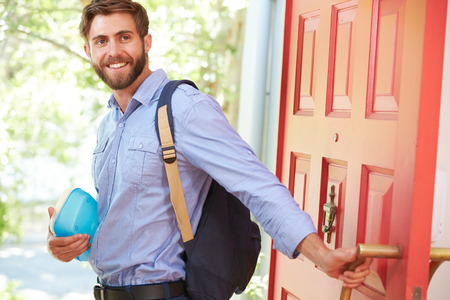 going in: Young Man Leaving Home For Work With Packed Lunch Stock Photo