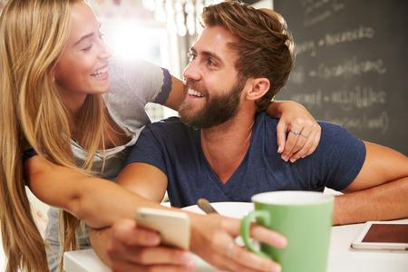 colazione: Coppia Eating Breakfast con tavoletta digitale e telefono