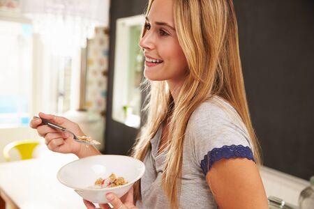 colazione: Giovane donna attraente mangia colazione Da Glass Bowl