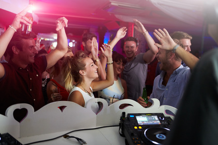 dancing club: People Dancing In Nightclub With DJ In Foreground Stock Photo