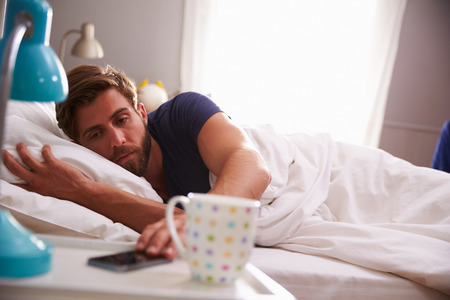 woken: Sleeping Man Being Woken By Mobile Phone In Bedroom Stock Photo