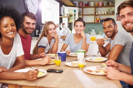 bacon portrait: Group Of Friends Enjoying Breakfast In Kitchen Together Stock Photo
