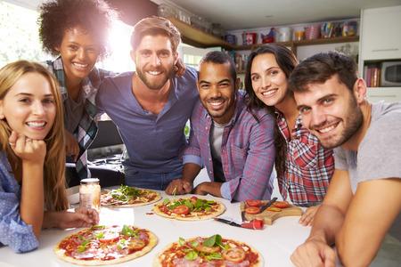 pareja comiendo: Grupo de amigos que hacen la pizza en cocina Juntos