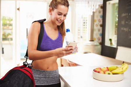 home gym: Woman Wearing Gym Clothing Looking At Mobile Phone