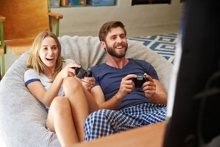 jugando videojuegos: Pareja joven en pijamas Jugar videojuegos Juntos
