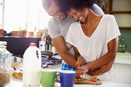 people sitting: Young Couple Preparing Breakfast In Kitchen Together Stock Photo